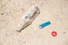 Bouteille en verre sur le sable jeté par la vague de mer pollution Concept d'écologie image libre de droits