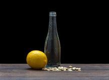 Bouteille en verre sur un fond noir, arachide et citron, la forme de la bouteille avec le citron et arachides le thème de Photos libres de droits
