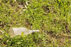 Bouteille en verre vide dans le domaine d'herbe, déchets images libres de droits