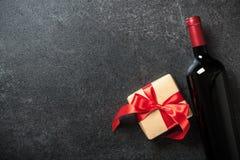 Bouteille et boîte-cadeau de vin rouge sur le fond noir Image stock