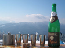 Bouteille et flacon avec quatre verres contre des montagnes photographie stock libre de droits