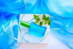 Bouteille et fleurs de parfum en verre bleues Image libre de droits