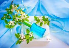 Bouteille et fleurs de parfum en verre bleues Images libres de droits