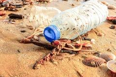 Bouteille et seashalls en plastique sur le sable humide jeté par la vague de mer images libres de droits