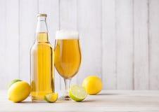 Bouteille et verre de bière blonde avec le citron et la chaux photos libres de droits