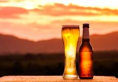 Bouteille et verre de bière blonde sur le coucher du soleil Images stock