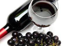 Bouteille et verre de vin avec des raisins noirs Photographie stock libre de droits