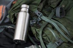 Bouteille inoxydable isolée avec le sac à dos militaire images stock