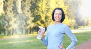 Bouteille mûre sportive de prise de femme avec de l'eau extérieur le jour ensoleillé en parc image libre de droits