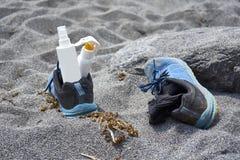 Bouteille neutre vide de protection solaire dans des espadrilles bleues sur SA noire Photo stock