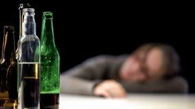 Bouteille ouverte d'alcool sur la table avec la femme de sommeil ivre sur le fond, désespoir images stock