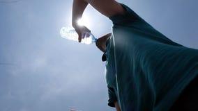 Bouteille potable de jeune homme de l'eau se tenant extérieure en été chaud clips vidéos