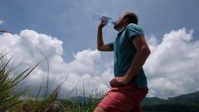 Bouteille potable de jeune homme de l'eau se tenant extérieure en été chaud banque de vidéos