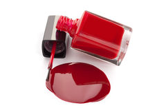 Bouteille rouge de vernis à ongles avec le vernis renversé Images libres de droits