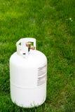 Bouteille simple de propane se reposant dans l'herbe avec des étiquettes de mise en garde Photo stock