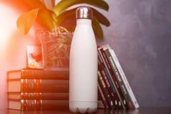 Bouteille thermo blanche avec la maquette vide au-dessus du fond des livres et de la fleur verte photos stock