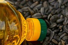 Bouteille transparente avec de l'huile de tournesol sur une pile des graines de tournesol Photos stock