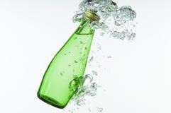 Bouteille verte éclaboussant dans l'eau Images stock
