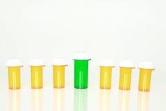 Bouteille verte parmi les bouteilles de pillule ambres Photo stock