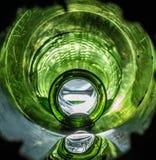 Bouteille verte vibrante lumineuse avec de l'eau sortant photographie stock