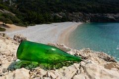 Bouteille verte vide se trouvant sur des roches près d'une plage photos libres de droits
