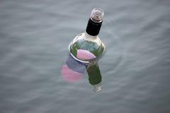 Bouteille vide flottant en rivière Image libre de droits