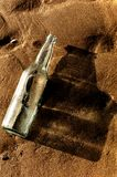 Bouteille vide sur le sable Image libre de droits