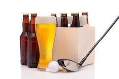 Bouteilles à bière avec le club et la bille de golf Image libre de droits
