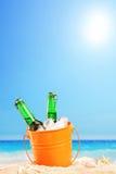Bouteilles à bière dans un seau de glace dans le sable sur une plage photos stock