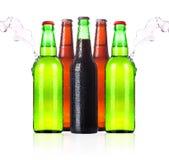 Bouteilles à bière givrées avec l'éclaboussure de l'eau   Images stock