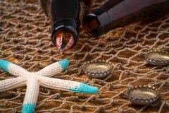 Bouteilles à bière vides sur une table superficielle par les agents Images stock