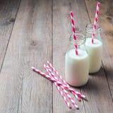 Bouteilles à lait avec de rétros pailles rayées Images libres de droits