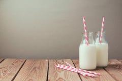 Bouteilles à lait avec de rétros pailles rayées sur la table en bois Photographie stock libre de droits