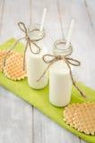 Bouteilles à lait avec des gaufres sur une serviette verte Image stock