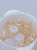 Bouteilles à lait dans le stérilisateur et le dessiccateur de vapeur image libre de droits