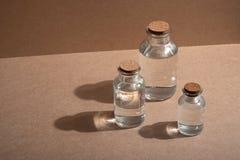 Bouteilles avec des chapeaux de liège sur un fond de carton marqué ou en bois en verre photographie stock