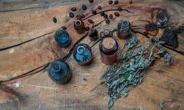 Bouteilles avec des liquides et herbes sur une table en bois Photographie stock
