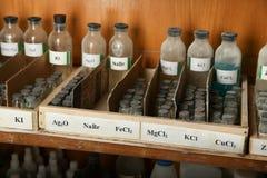 Bouteilles avec des solutions de NaBr, FeCl2, mgcl2 sur l'étagère de l'armoire chimique image libre de droits