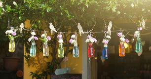 Bouteilles avec l'eau colorée et des fleurs accrochant sur une ficelle sur le fond de rue d'été photographie stock libre de droits