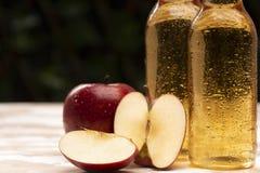 Bouteilles avec le cidre près du panier avec des pommes Photos libres de droits