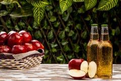 Bouteilles avec le cidre près du panier avec des pommes Photographie stock