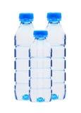 Bouteilles bleues avec de l'eau d'isolement sur le blanc Image libre de droits