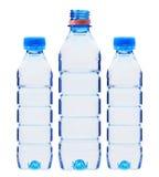 Bouteilles bleues avec de l'eau d'isolement sur le blanc Photographie stock libre de droits