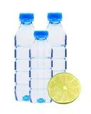 Bouteilles bleues avec l'eau et la chaux verte fraîche d'isolement sur le blanc Photographie stock
