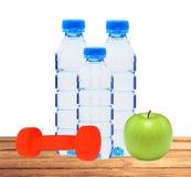 Bouteilles bleues avec l'eau, le dumbell et la pomme verte sur l'isolat de table Photos libres de droits