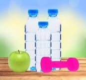 Bouteilles bleues avec l'eau, le dumbell et la pomme verte sur la table au-dessus de n Photo stock