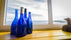 Bouteilles bleues dans une fenêtre près de la mer, Canada de Terre-Neuve Photos stock