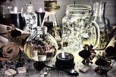 Bouteilles brillantes, cuillère, vieilles racines et parchemins sur la table de sorcière photographie stock libre de droits