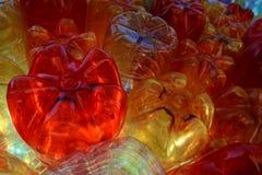 Bouteilles claires jaunes rouges de plast Photographie stock