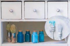 Bouteilles colorées avec des peintures, des brosses et un plat en céramique fait main sur l'étagère en bois, concept de dessin Photo libre de droits